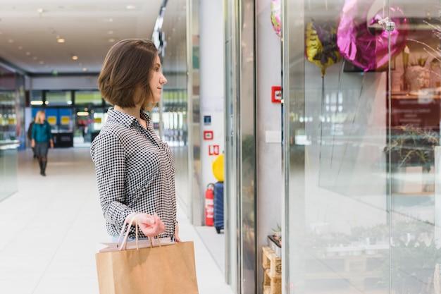 Mulher jovem, segurando, bolsas para compras Foto gratuita
