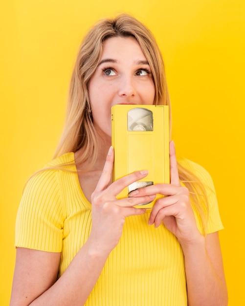 Mulher jovem, segurando cassete Foto gratuita