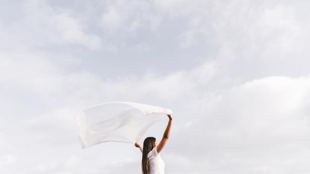 Mulher jovem, segurando, echarpe, soprar vento, contra, céu Foto gratuita