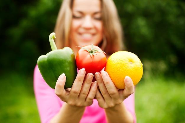 Mulher jovem segurando frutas e vegetais Foto gratuita