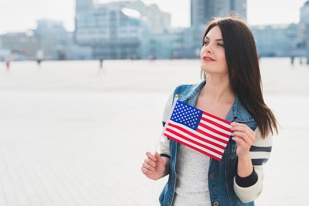 Mulher jovem, segurando, pequeno, bandeira americana, durante, celebração, de, dia independência Foto gratuita