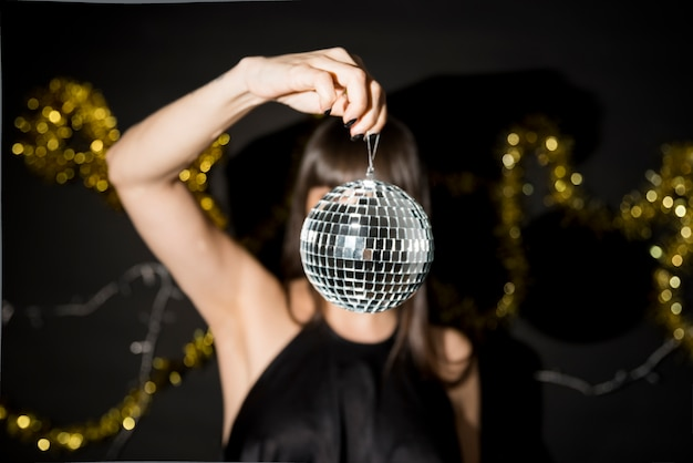 Mulher jovem, segurando, pequeno, discoteca, bola, perto, ouropel Foto gratuita
