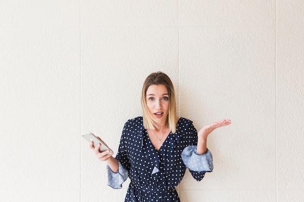 Mulher jovem, segurando, smartphone, ficar, frente, parede, shrugging Foto gratuita