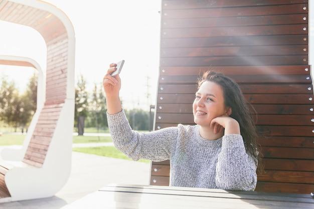 Mulher jovem, segurando, telefone, em, mão, parque Foto Premium