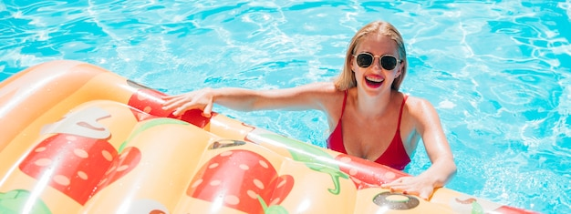 Mulher jovem, segurando, um, pizza, natação, flutuador Foto gratuita