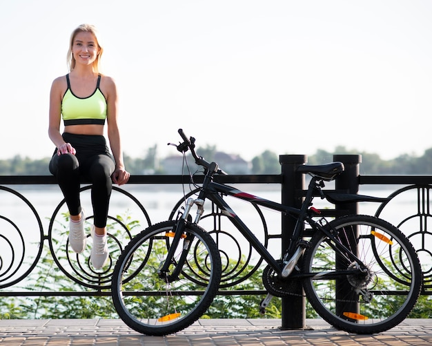 Mulher jovem sentada em uma cerca ao lado de sua bicicleta Foto Premium