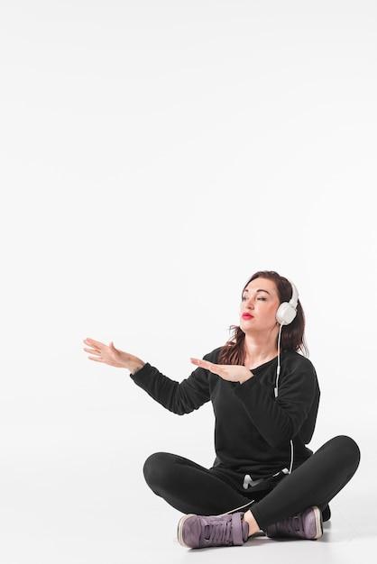 Mulher jovem, sentando, com, cruzado, perna, desfrutando, música, ligado, headphone, dançar Foto gratuita