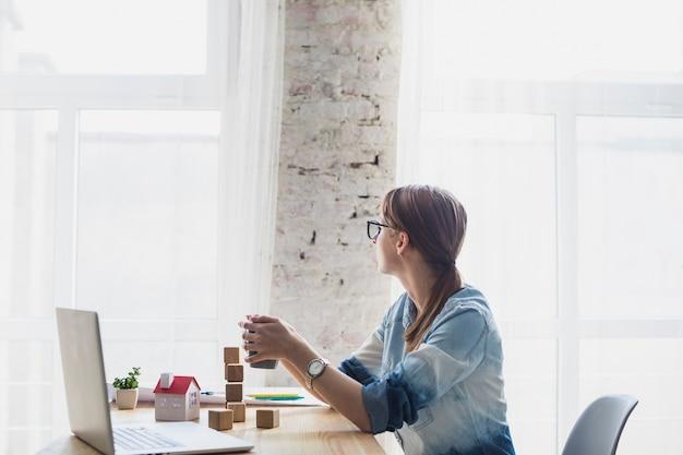 Mulher jovem, sentando, em, escritório, segurando, xícara café, em, mão Foto gratuita