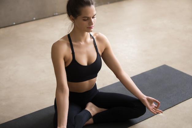 Mulher jovem, sentando, em, sukhasana, pose, com, mudra, cinzento, estúdio Foto gratuita