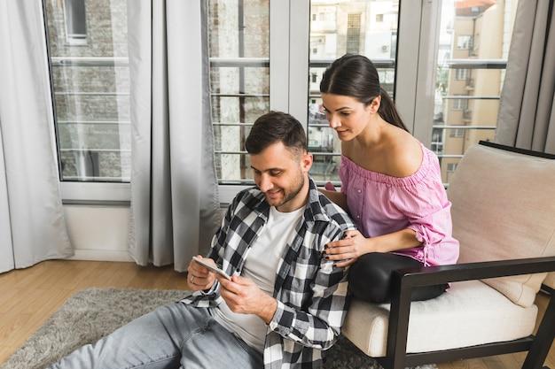 Mulher jovem, sentando, ligado, cadeira, olhar, dela, namorado, usando, telefone móvel, casa Foto gratuita