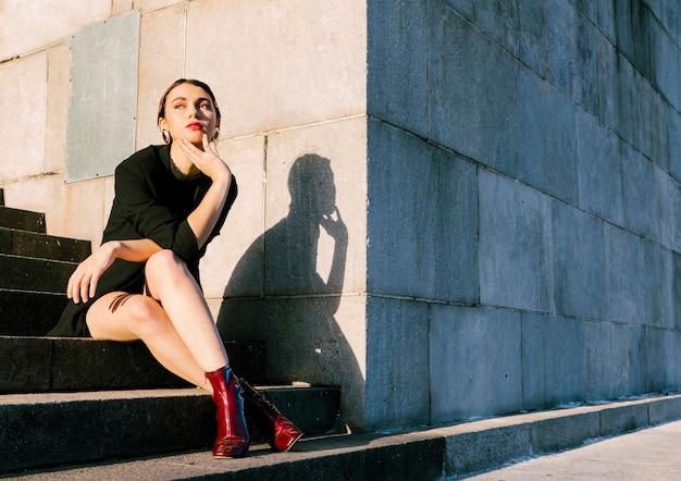 Mulher jovem, sentando, ligado, escadaria, em, luz solar Foto gratuita