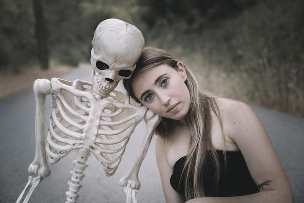 Mulher jovem, sentando, ligado, estrada, com, esqueleto Foto gratuita