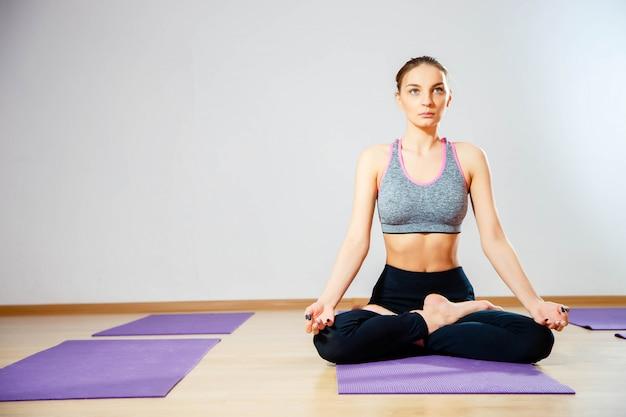 Mulher jovem, sentar chão, em, posição lotus, enquanto, meditar Foto Premium