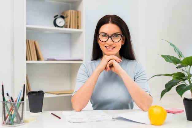 Mulher jovem, sentar-se tabela, em, escritório Foto gratuita