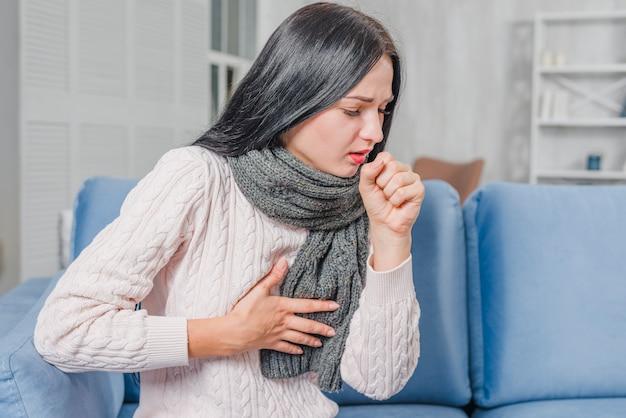 Mulher jovem, sentar sofá azul, sofrimento, de, sofá, tendo, dor peito Foto gratuita
