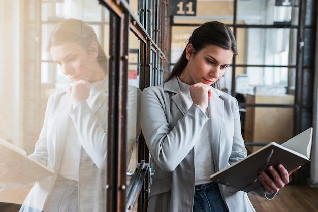 Mulher jovem séria olhando diário no escritório Foto gratuita