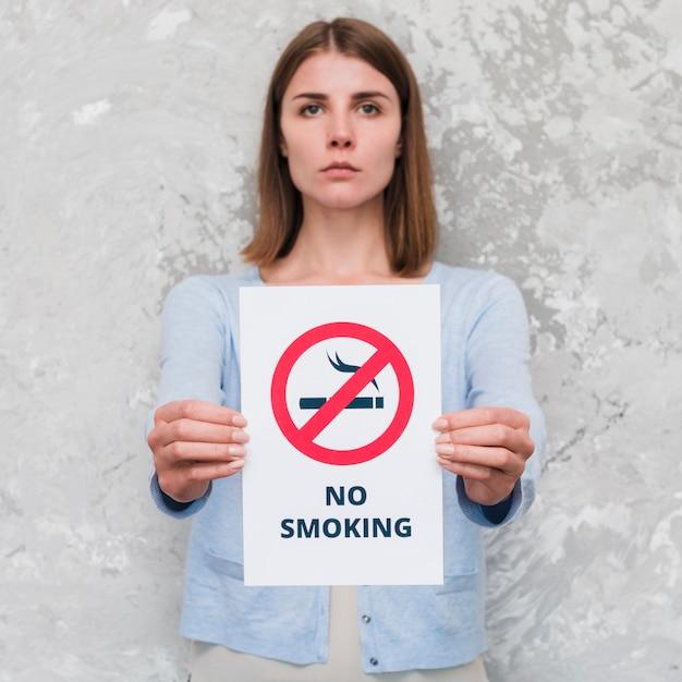 Mulher jovem séria segurando papel de mensagem social de não fumar Foto gratuita