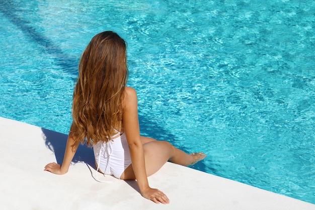 Mulher jovem sexy de cabelos compridos com maiô branco sentada relaxando na piscina Foto Premium