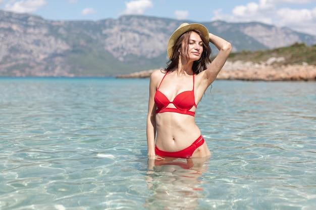 Mulher jovem sexy em pé na água do mar Foto gratuita