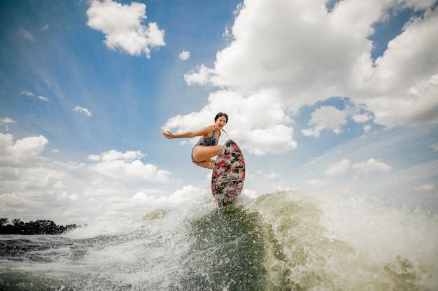 Mulher jovem sexy se divertindo wakesurfing anf pulando no quadro Foto Premium