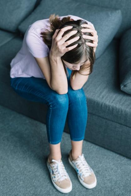 Mulher jovem, sofrimento, de, dor de cabeça, sentar sofá Foto gratuita