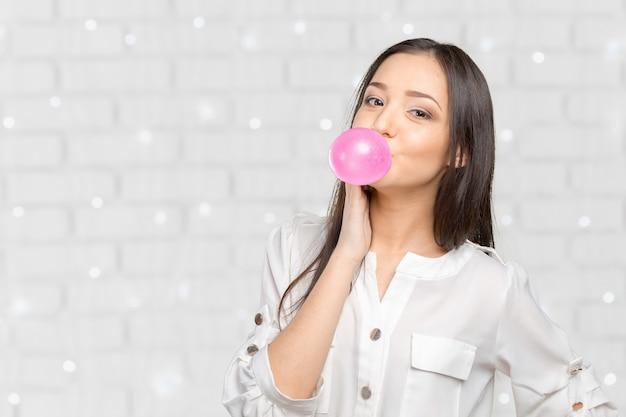 Mulher jovem, soprando, bubblegum Foto Premium