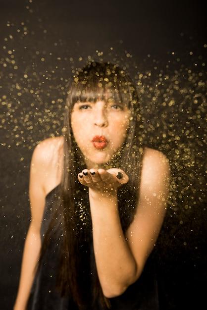 Mulher jovem, soprando, confetti, de, mão Foto gratuita