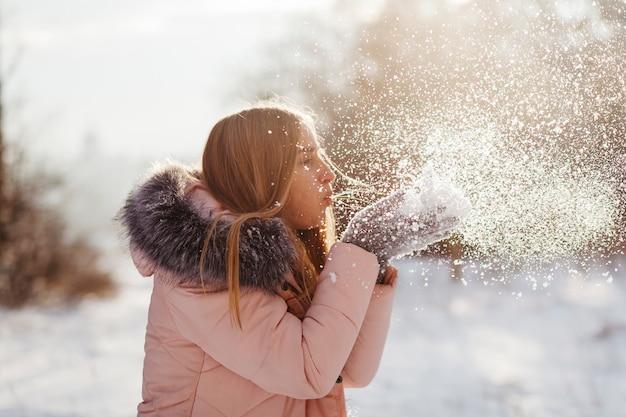 Mulher jovem, soprando, neve, de, mãos Foto gratuita