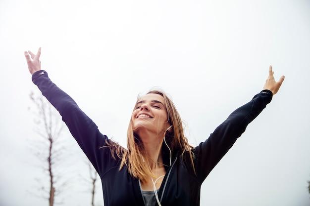 Mulher jovem sorridente com smartphone e fones de ouvido, ouvindo música Foto Premium