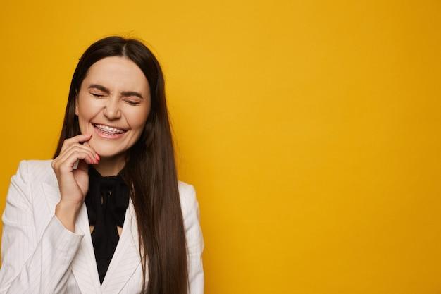 Mulher jovem sorridente no aparelho dental posando com os olhos fechados Foto Premium