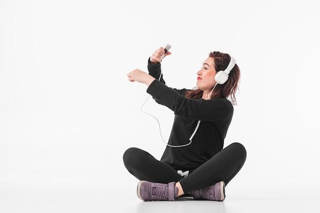 Mulher jovem sorridente ouvindo música no mp3 player Foto gratuita