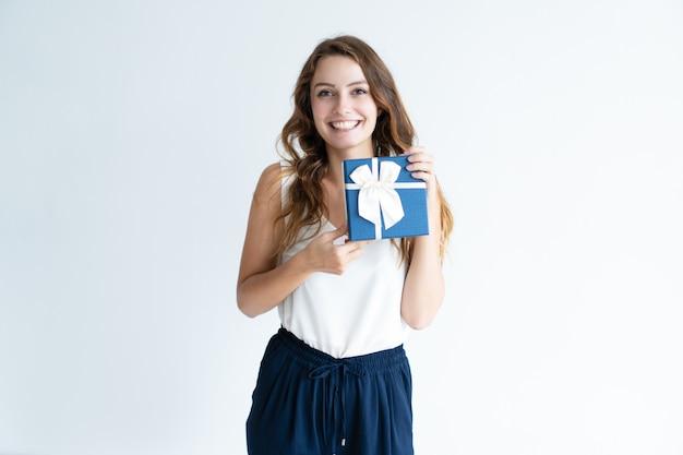 Mulher jovem sorridente segurando a caixa de presente com laço de fita Foto gratuita