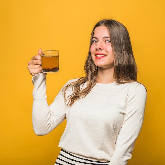 Mulher jovem sorridente segurando a xícara de chá de ervas na mão de pé contra o pano de fundo amarelo Foto gratuita