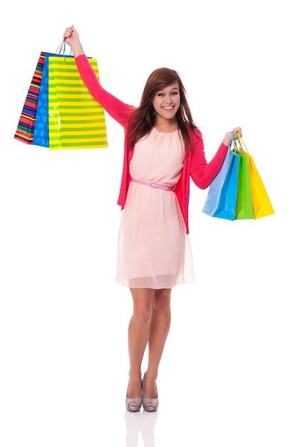Mulher jovem sorridente segurando sacolas de compras Foto gratuita