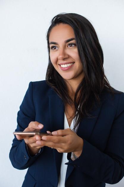 Mulher jovem sorridente, segurando telefone móvel Foto gratuita