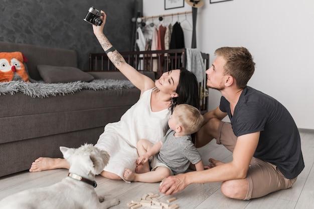 Mulher jovem sorridente tomando selfie de sua família enquanto está sentado na sala de estar Foto gratuita