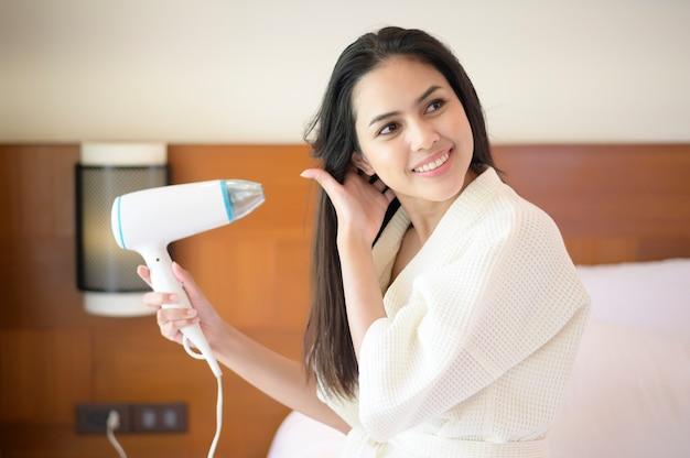 Mulher jovem sorridente usando roupão de banho branco, secando o cabelo com secador de cabelo após o banho no quarto Foto Premium