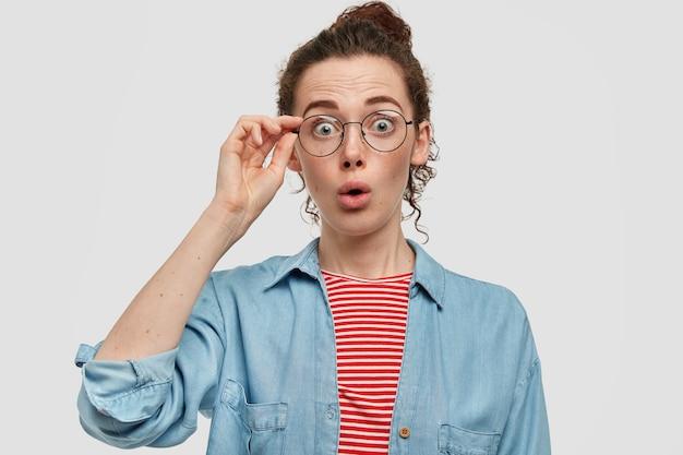Mulher jovem surpreendida com rosto sardento, olha em choque, usa óculos, fica maravilhada, vestida com um suéter vermelho listrado e camisa jeans, testemunhou um acidente chocante. conceito de espanto Foto gratuita