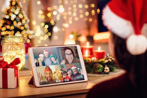 Mulher jovem, tendo uma videochamada de natal com sua família feliz. conceito de famílias em quarentena por causa do coronavírus Foto Premium