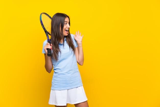 Mulher jovem tenista isolado parede amarela com expressão facial de surpresa Foto Premium