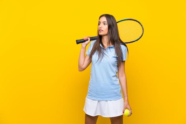 Mulher jovem tenista sobre parede amarela isolada Foto Premium