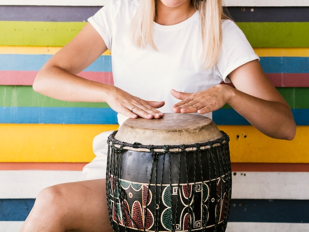Mulher jovem, tocando, yuker, tambor Foto gratuita