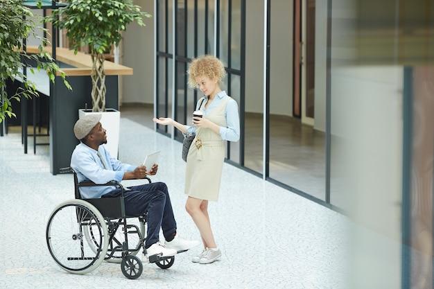 Mulher jovem tomando café e conversando com um homem africano que, sentado em uma cadeira de rodas, está no shopping Foto Premium