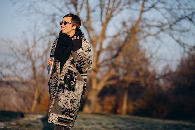 Mulher jovem tomando café pela manhã e caminhando no parque Foto gratuita
