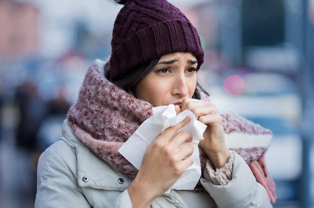 Mulher jovem tossindo durante o inverno na rua Foto Premium