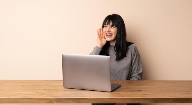 Mulher jovem, trabalhando, com, dela, laptop, shouting, com, boca largo aberto, para, a, lateral Foto Premium