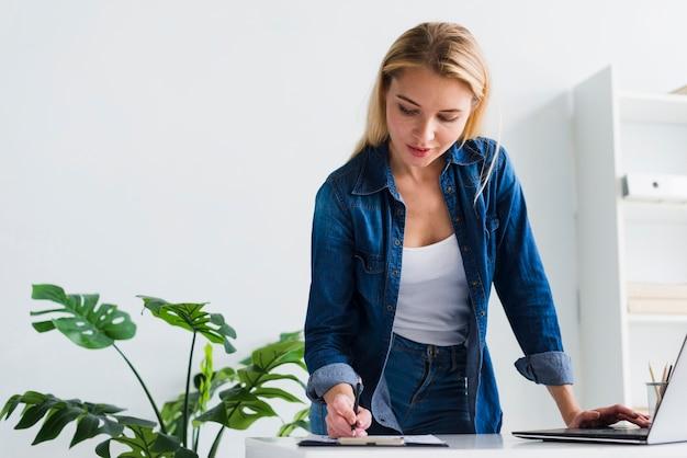Mulher jovem, trabalhando, com, documentos, em, escritório Foto gratuita