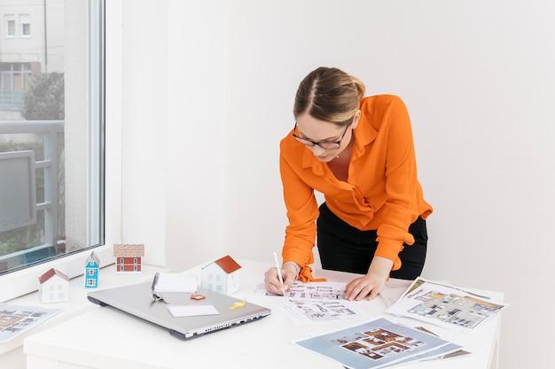 Mulher jovem, trabalhando, ligado, blueprint, escrivaninha Foto gratuita