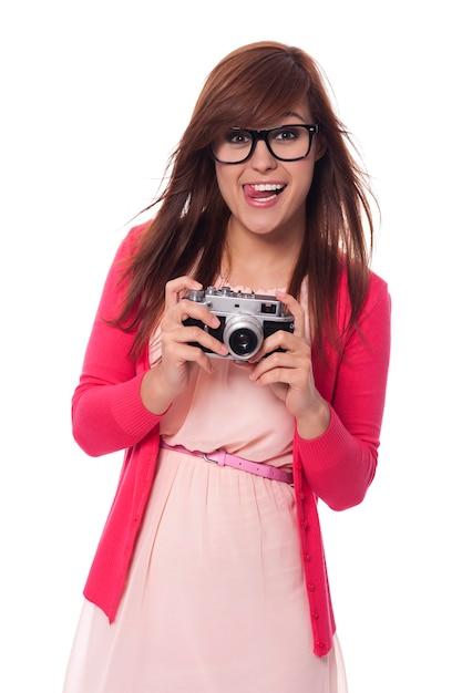 Mulher jovem travessa com câmera vintage Foto gratuita