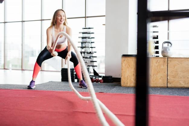 Mulher jovem treinando com corda de batalha em ginásio cross fit Foto gratuita
